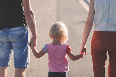 little girl holding parents hands with family life insurance